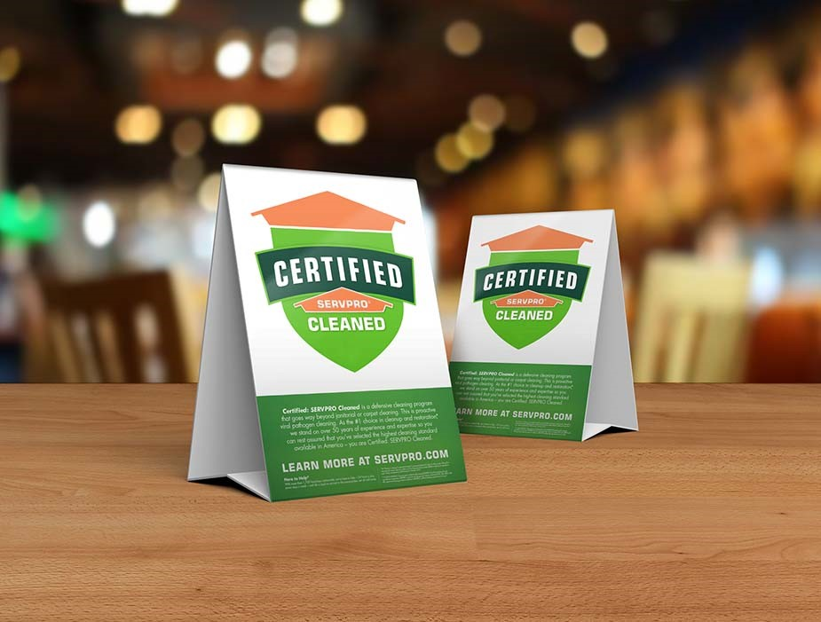 table tents describing the Certified: SERVPRO Cleaned program on top of a wooden table